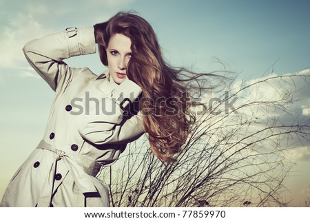 Fashion portrait of elegant woman in a raincoat on the nature - stock photo