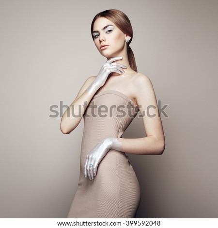 Fashion portrait of elegant woman with magnificent hair. Blonde girl. Perfect make-up. Girl in elegant dress. Girl posing. Studio photo - stock photo