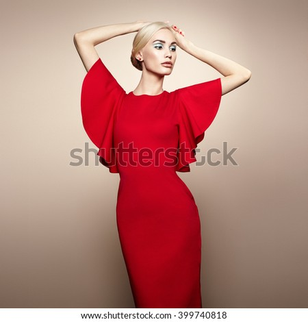 Fashion portrait of elegant woman with magnificent hair. Blonde girl. Perfect make-up. Girl in elegant red dress. Girl posing. Studio photo - stock photo