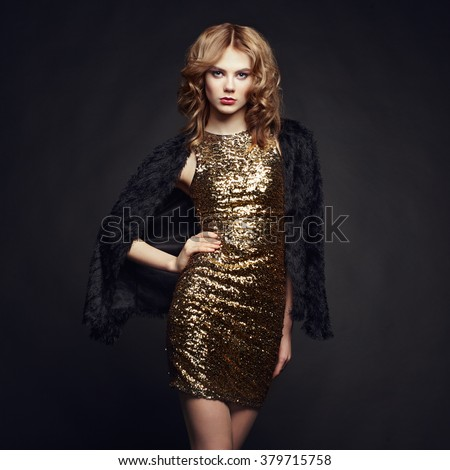 Fashion portrait of elegant woman with magnificent hair. Blonde girl. Perfect make-up. Girl in gold dress on black background - stock photo
