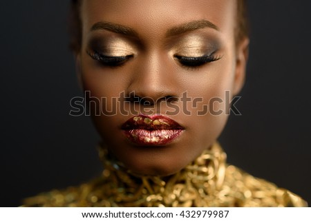 Fashion Portrait of Glossy African American Woman with Bright Golden Makeup. Bronze Bodypaint, Black Studio Background