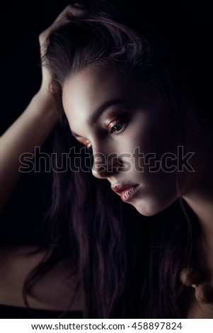 Fashion portrait of gorgeous young brunette woman. Shallow depth of field. Low key portrait on black