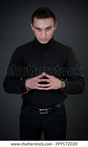 Fashion portrait of handsome man in black shirt poses in the studio - stock photo