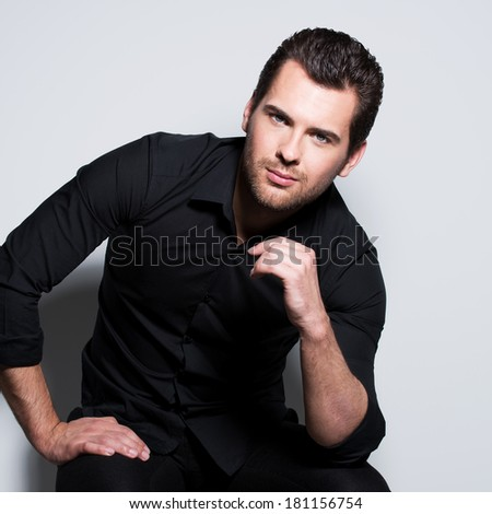 Fashion portrait of handsome man in black shirt with hand near face poses in the studio. - stock photo
