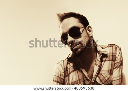 Fashion portrait of handsome young man wearing sunglasses on white background