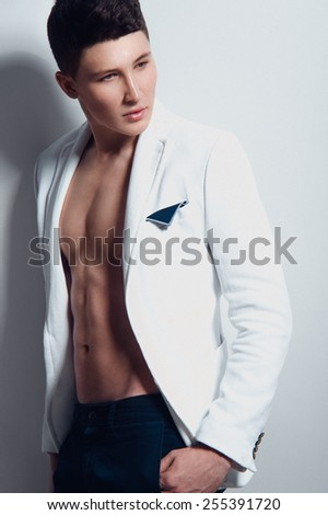 Fashion portrait of handsome young man with nude muscular body, in white jacket and dark jeans, with arms in his pockets looking to the right on white background - stock photo