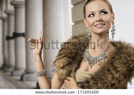 fashion portrait of happy aristocratic woman with blonde elegant hair-style, fur shawl and shiny diamond jewellery. She smiling