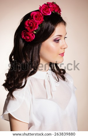 Fashion portrait of happy pretty brunette teenager girl is wearing white blouse and red roses wreath on her head - stock photo
