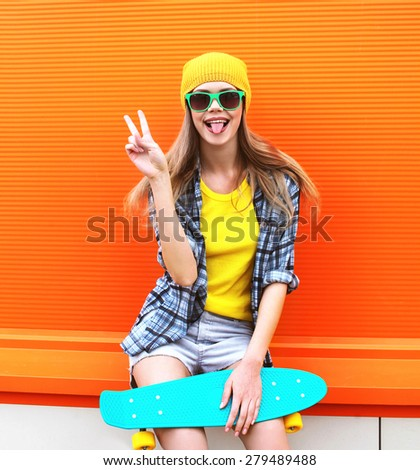 Fashion portrait of hipster cool girl in sunglasses and colorful clothes with skateboard having fun against the orange wall - stock photo