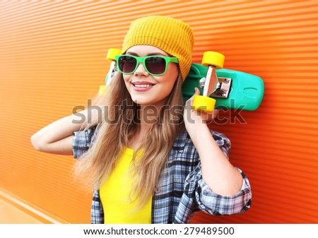 Fashion portrait of hipster cool girl in sunglasses with skateboard having fun outdoors against the colorful orange wall - stock photo