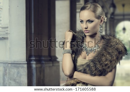 fashion portrait of luxury blonde girl posing with elegant hair-style, fur shawl and precious shiny jewellery. Cute make-up  - stock photo