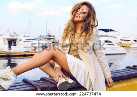 Fashion portrait of luxury sexy blonde girl posing near yacht club in white stylish cashmere coat, golden top sneakers and sunglasses.Bright colors. - stock photo