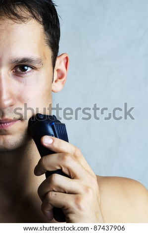 Fashion portrait of man shaving chin and cheek by electric shaver. Male hygiene. Copy space for your text - stock photo