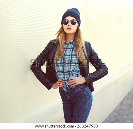 Fashion portrait of pretty blonde girl in trendy rock style posing outdoors - stock photo
