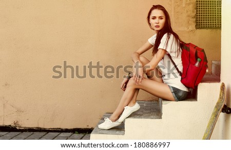Fashion portrait of pretty brunette woman with skateboard and red backpack. Hipster young style girl posing on creamy background