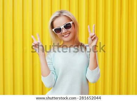 Fashion portrait of pretty cool smiling girl in sunglasses having fun against the colorful yellow wall - stock photo