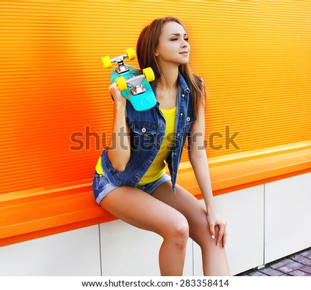 Fashion portrait of pretty girl in colorful clothes with skateboard against the orange wall - stock photo