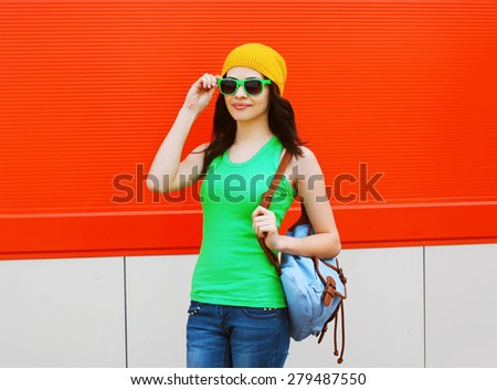 Fashion portrait of pretty girl in sunglasses and colorful clothes with backpack outdoors against the red wall - stock photo