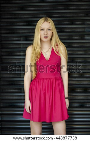 Fashion portrait of pretty sexy young blonde woman posing on dark wall background  - stock photo