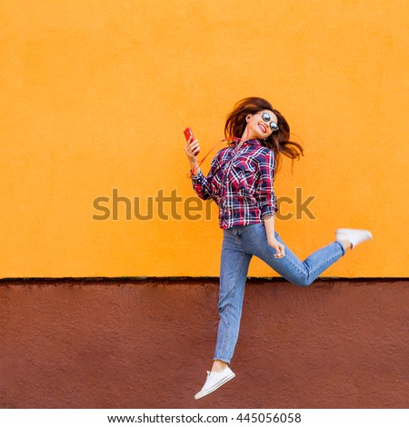 Fashion portrait of pretty smiling and jumping woman in sunglasses with smartphone against the colorful orange wall. Copyspace - stock photo