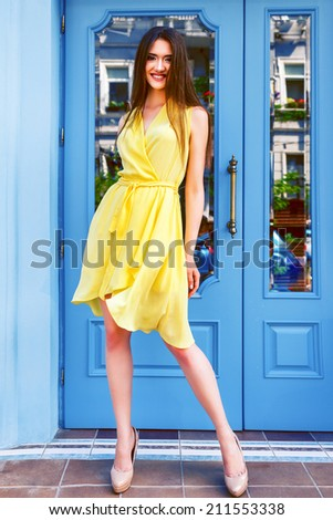 Fashion portrait of pretty smiling woman posing near restaurant door in elegant midi pastel yellow dress and nude pumps. Bright colors. - stock photo