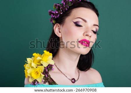Fashion portrait of pretty teen girl with purple wreath of flowers in hair and fashion makeup is holding daffodil flowers in hands - stock photo