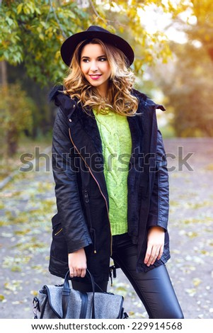 Fashion portrait of pretty young blonde smiling woman wearing trendy coat, vintage hat and neon sweater, posing at countryside park in nice sunny fall autumn day. - stock photo