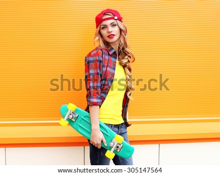 Fashion portrait of pretty young woman in red checkered hipster shirt, cap with skateboard against the colorful orange background - stock photo