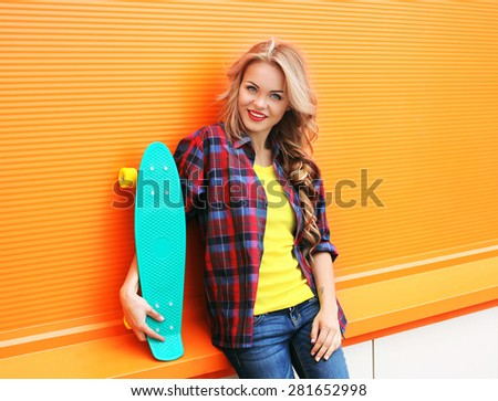 Fashion portrait of pretty young woman in red checkered hipster shirt with skateboard against the colorful orange wall - stock photo