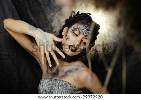 fashion portrait of pretty young woman with creative make up like a snake - stock photo