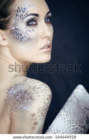 fashion portrait of pretty young woman with creative make up like a snake, fashion victim with python skin clutch - stock photo