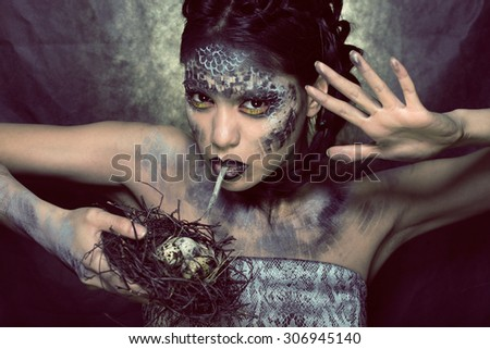fashion portrait of pretty young woman with creative make up like a snake halloween - stock photo