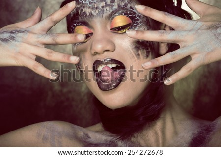 fashion portrait of pretty young woman with creative make up like a snake, halloween look - stock photo