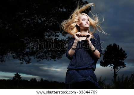 Fashion portrait of romantic woman with magnificent hair in fairy forest
