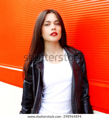 Fashion portrait of sexy beautiful brunette woman with red lipstick wearing a rock black leather jacket outdoors in the city against the colorful wall - stock photo