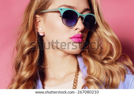 Fashion portrait of sexy beautiful woman with blond curly hair, bright makeup wearing a blue coat,sunglasses and posing on a pink background around the trees - stock photo