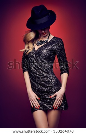 Fashion portrait of sexy beauty woman in stylish sequins dress, black hat. Unusual creative provocative. Emotional playful blonde glamour girl, luxury necklace, evening elegant party on red, people - stock photo