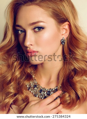 Fashion portrait of sexy blond girl with curly hair wearing beautiful jewelry and posing at studio