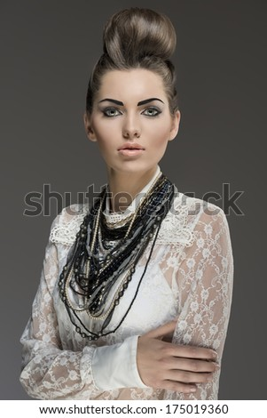 fashion portrait of sexy brunette with elegant hair-style and a lot of necklaces. Wearing  white lace shirt and looking in camera