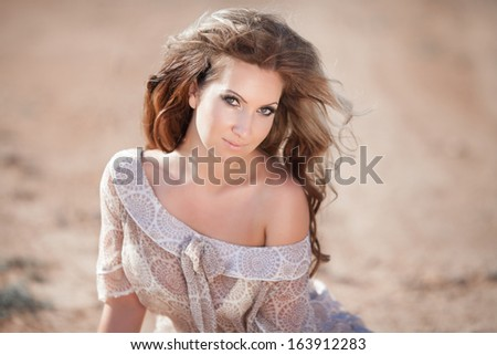 fashion portrait of sexy delicate woman, vogue style girl with long curly hair outdoors. Portrait of young sensual woman. Tan Woman in salty desert.