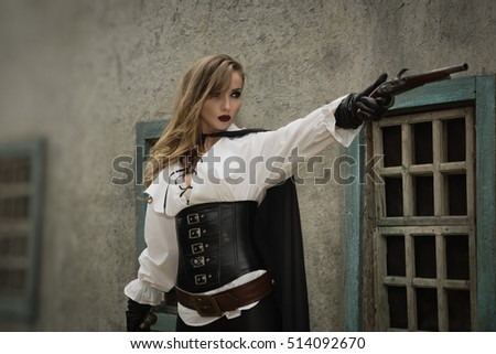 Fashion portrait of sexy woman in pirate style with old handgun