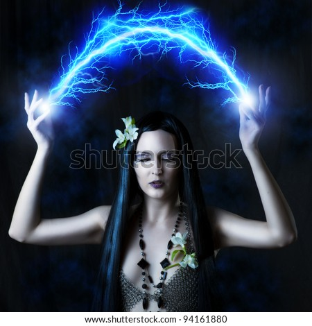 Fashion portrait of sexy woman - witch or elf. She is making magic - arc or flash lightning - stock photo