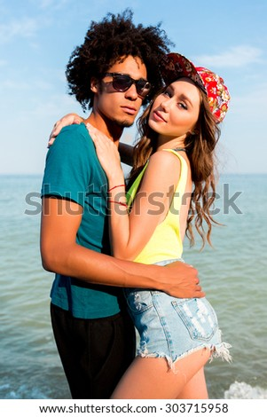 Fashion portrait of stylish  couple  posing on amazing tropical beach. Pretty sexy  slim tan woman and her handsome man looking at camera. Wearing  bright neon   swimwear and  hight jeans shorts . - stock photo
