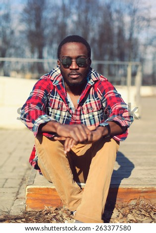 Fashion portrait of stylish young african man listens to music outdoors, wearing a plaid hipster red shirt and sunglasses - stock photo