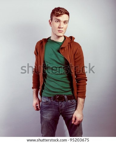 Fashion portrait of the young beautiful man in studio - stock photo