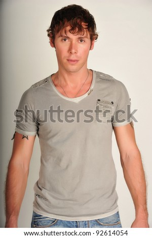 Fashion portrait of the young beautiful man in white t-shirt posing over gray background, series photo