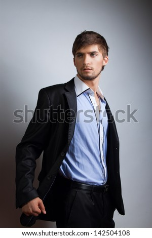 Fashion portrait of the young beautiful man over gray background - stock photo