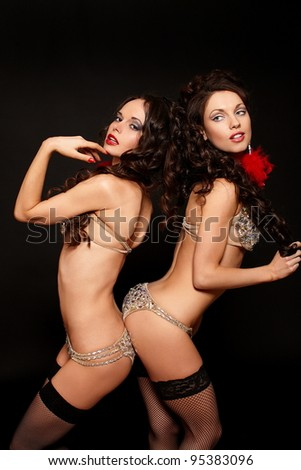 fashion portrait of two sexy brunette girls in light lingerie with long curly hair and jewelery bright makeup red lips isolated on black - stock photo