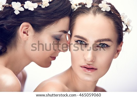 Fashion portrait of two young brunette woman on white. Shallow depth of field
