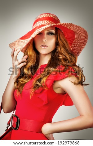 Fashion portrait of woman wearing vogue red hat and dress isolated on gray background - stock photo